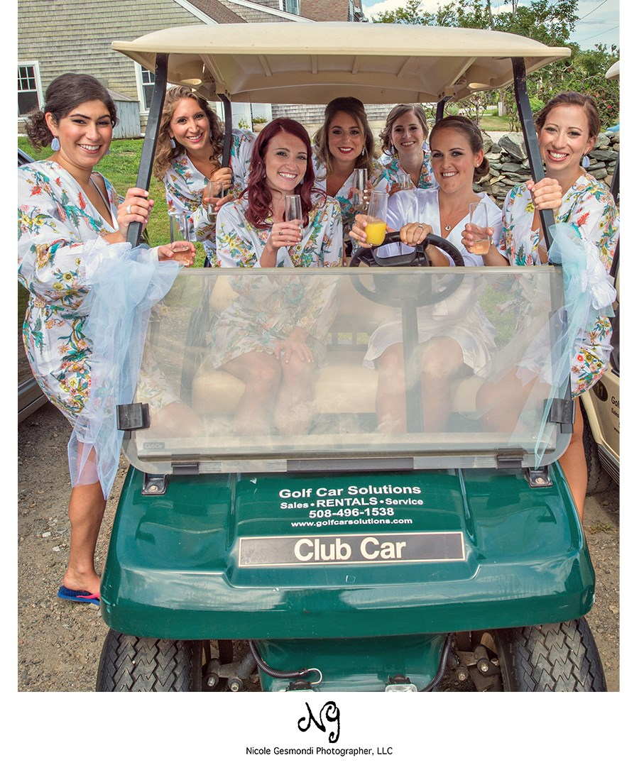 Bride with bridesmaids wearing matching robes and drinking champagne on a golf cart