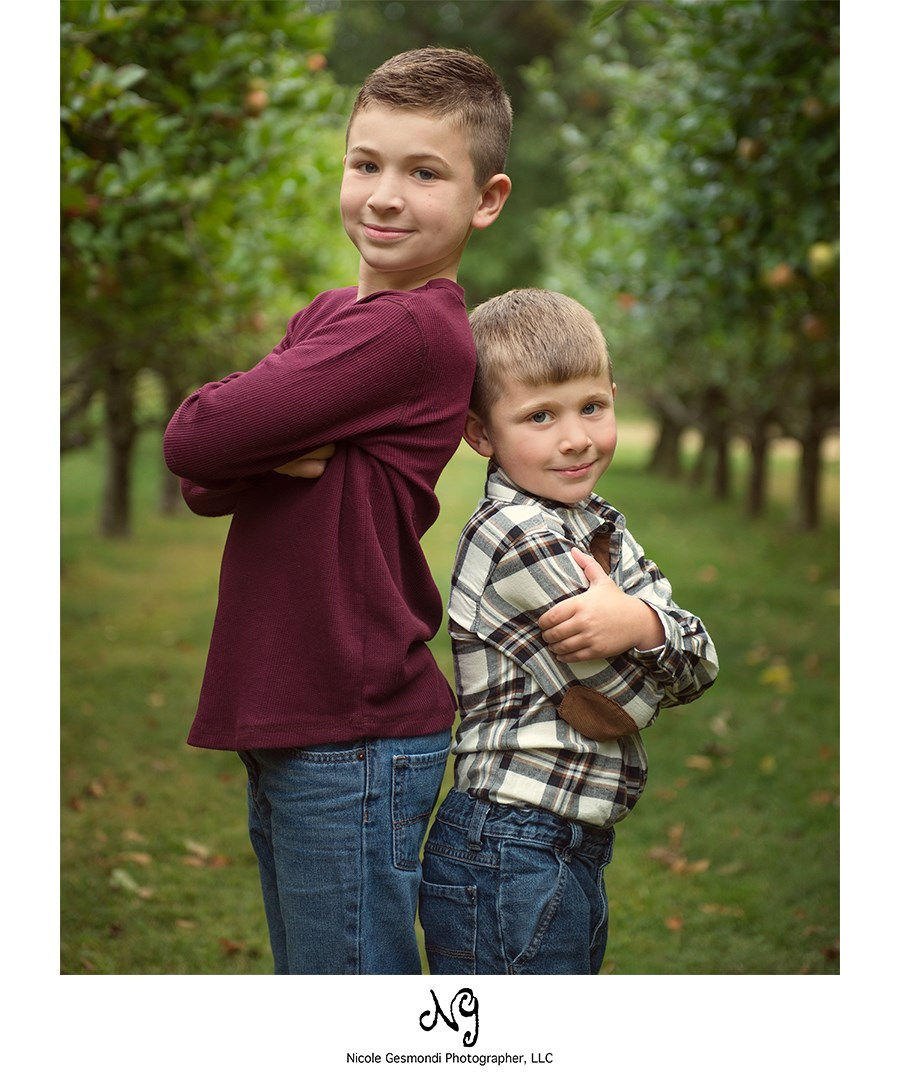 two brothers standing back to back in an apply orchard