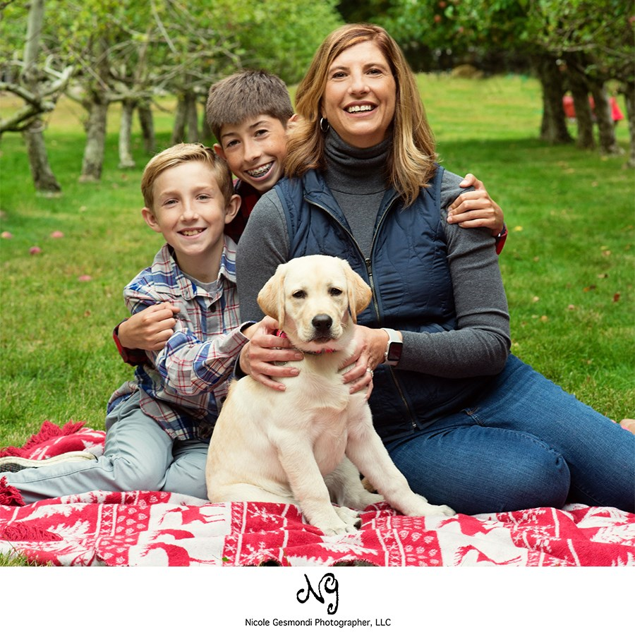 family sitting on a blanket with a dog