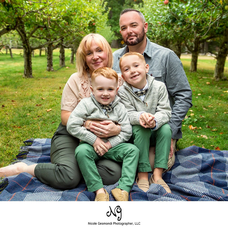 family sitting on a blanket at an apple orchard