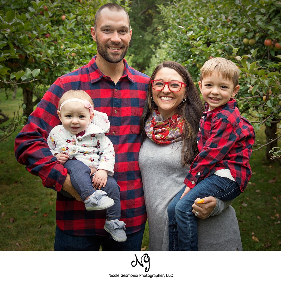 family wearing matching red plaid outfits for fall photos
